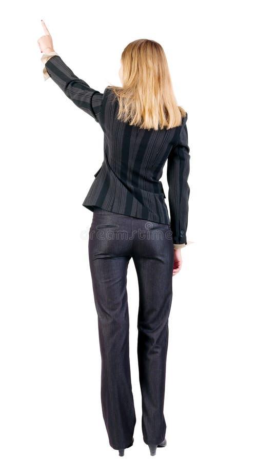 指向墙壁的后面观点的年轻白肤金发的女商人。 库存照片