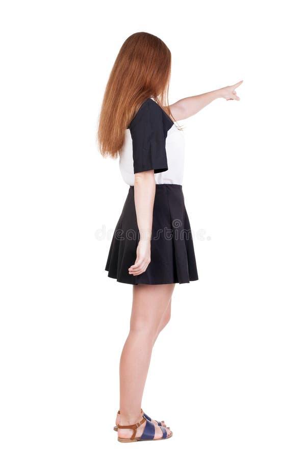 指向墙壁的后面观点的年轻红头发人妇女 美好的gir 库存照片