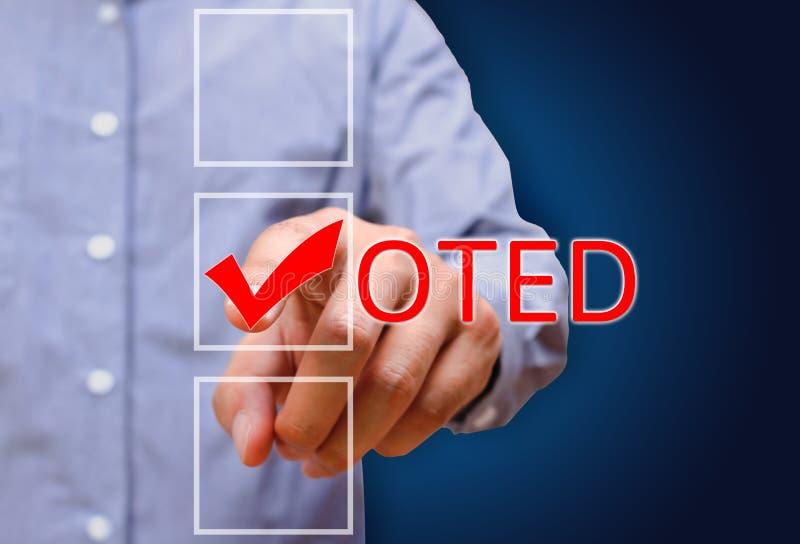指向壁虱标记,投票的标志的年轻商人 免版税库存照片