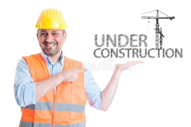 指向大厦起重机的微笑的建筑师 免版税库存图片