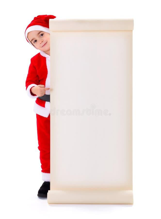 指向大愿望的小圣诞老人男孩 库存照片