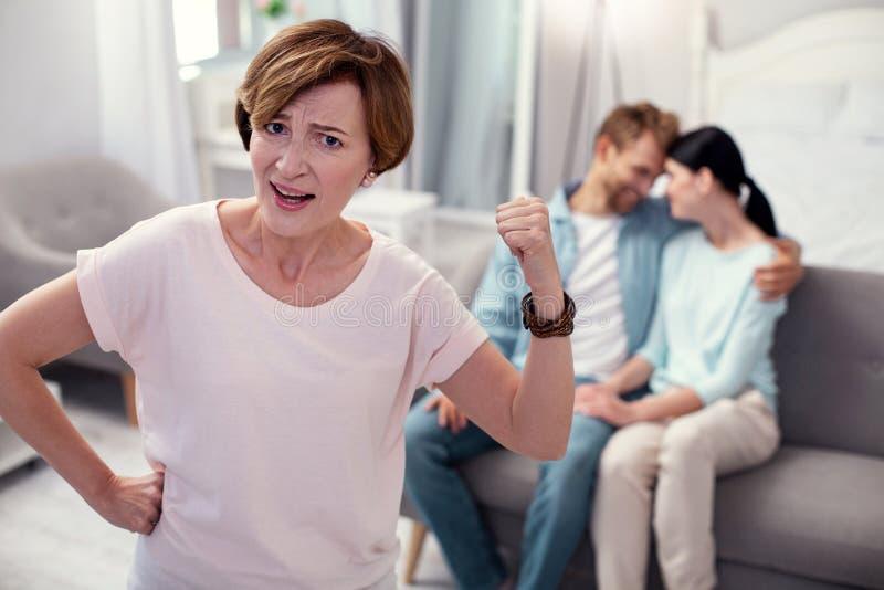 指向夫妇的不快乐的年迈的妇女 免版税库存照片