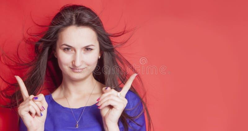指向她的往拷贝空白区的美丽的年轻女人画象手指反对红色背景 图库摄影