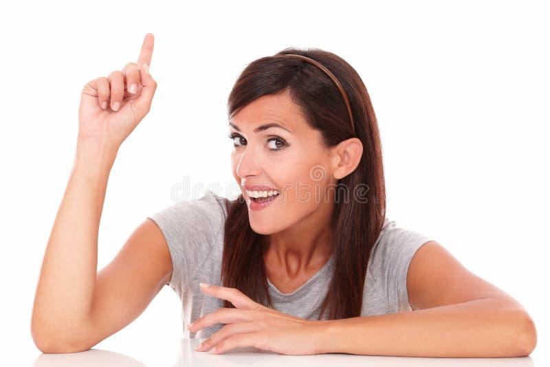 指向她的手指的成人愉快的女性 免版税库存照片