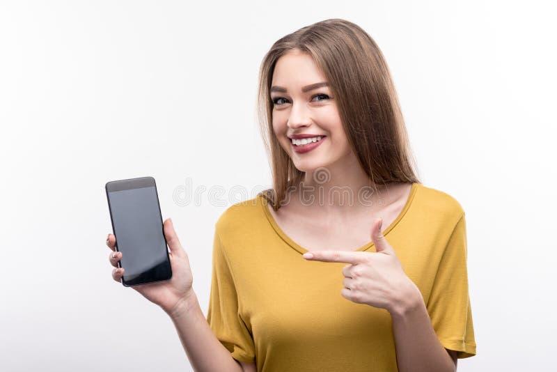 指向她的手机的逗人喜爱的少妇 库存图片