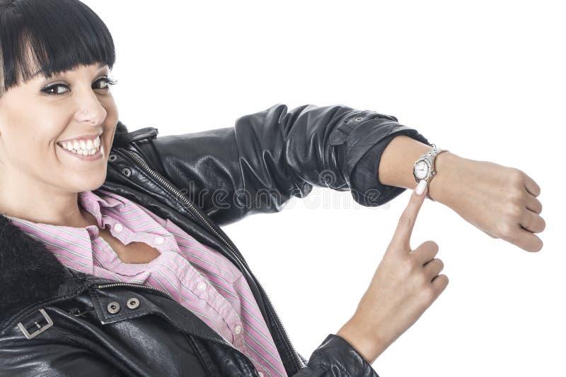 指向她的手表的愉快的高兴少妇 免版税库存照片