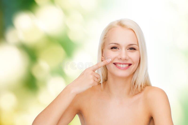 指向她的鼻子的微笑的少妇 免版税库存照片