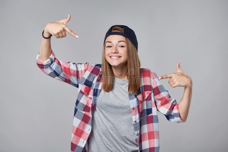 指向她自己的微笑的青少年的女孩 库存照片