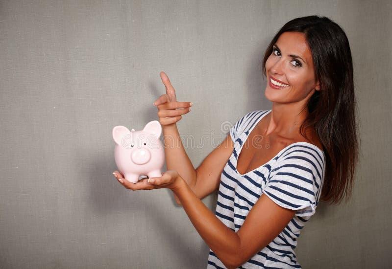 指向存钱罐的愉快的年轻人 图库摄影
