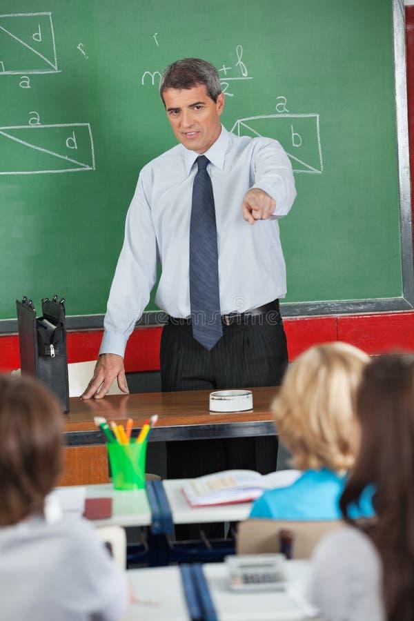 指向学生的成熟老师 免版税库存图片