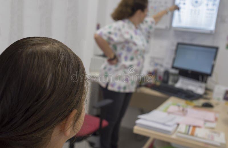 指向孩子的视力检查表的眼科医生手Healt 免版税图库摄影