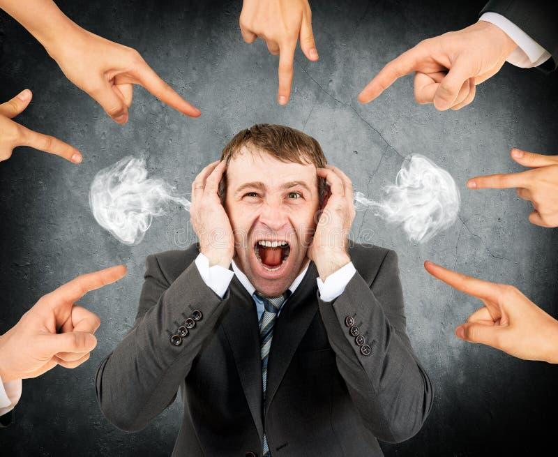 指向尖叫的手指被注重的商人 库存照片