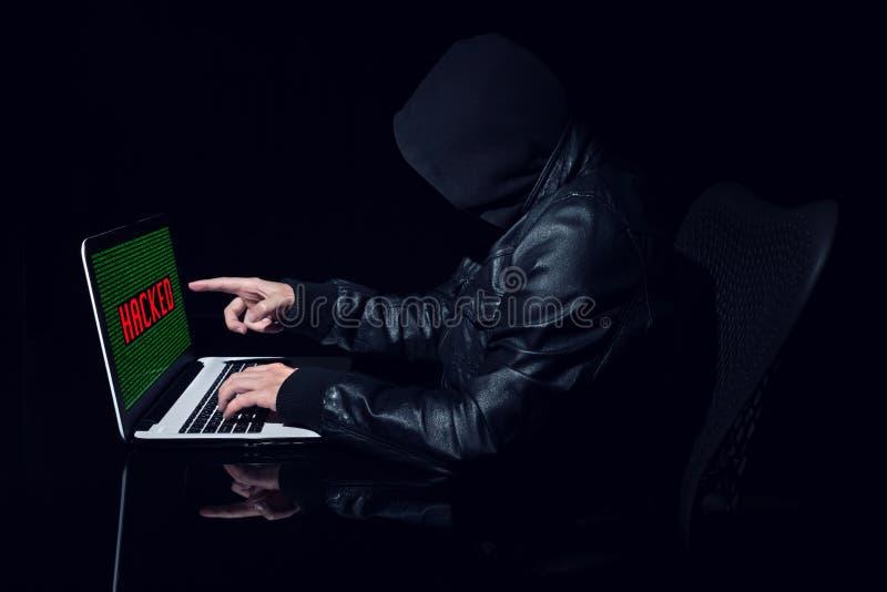 指向屏幕的匿名黑客 免版税库存图片