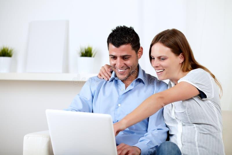 指向屏幕的夫妇膝上型计算机微笑年轻人 库存照片