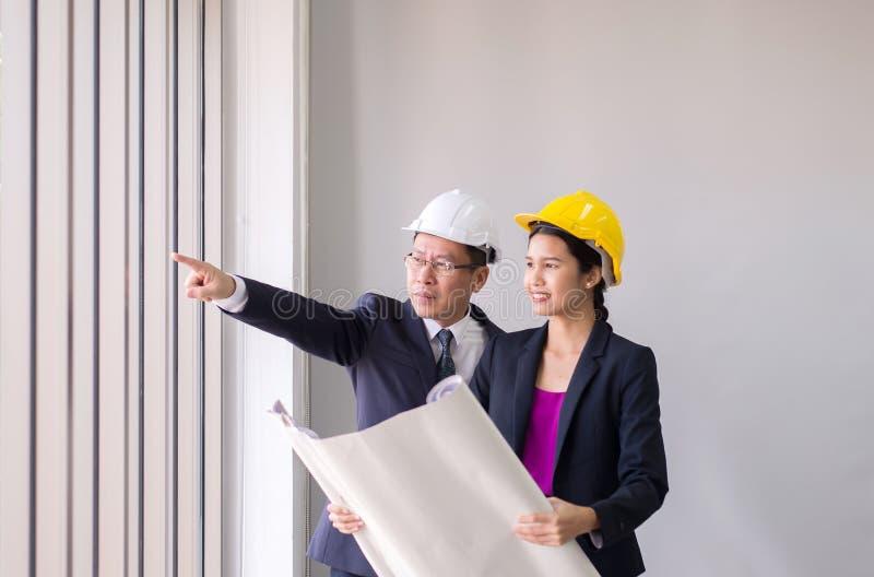 指向工作的夫妇亚洲工头手expertising有方案的,选择聚焦structureon工地工作 免版税库存图片
