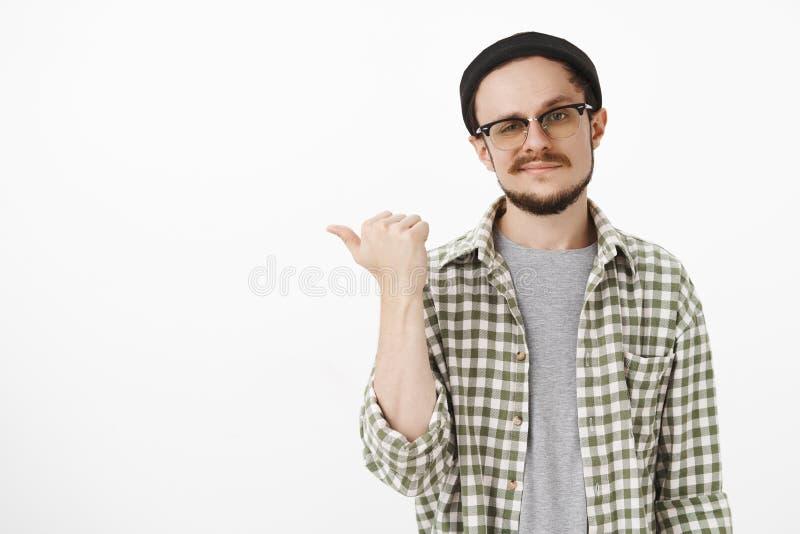 指向工友的熟练的创造性的人有产品的高兴的帮助顾客 演播室被射击英俊自信 免版税图库摄影