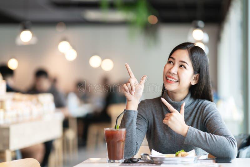 指向年轻可爱的亚裔的妇女和查寻上面支持显示感觉愉快的消息惊奇 库存照片