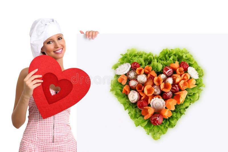 指向广告牌沙拉心脏形状的概念素食饮食厨师妇女 免版税库存照片