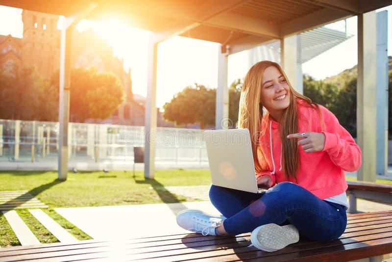 指向开放膝上型计算机的迷人的白肤金发的女学生 免版税图库摄影