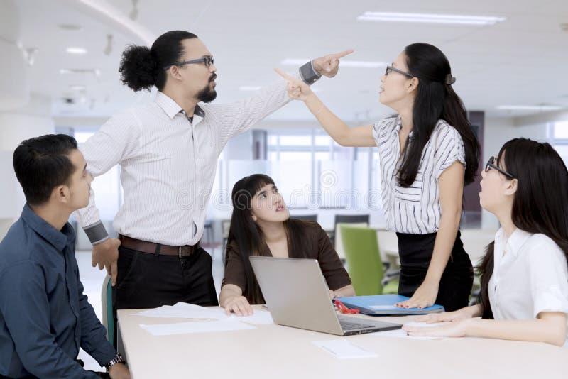 指向彼此的商人有论据在小组会议 图库摄影