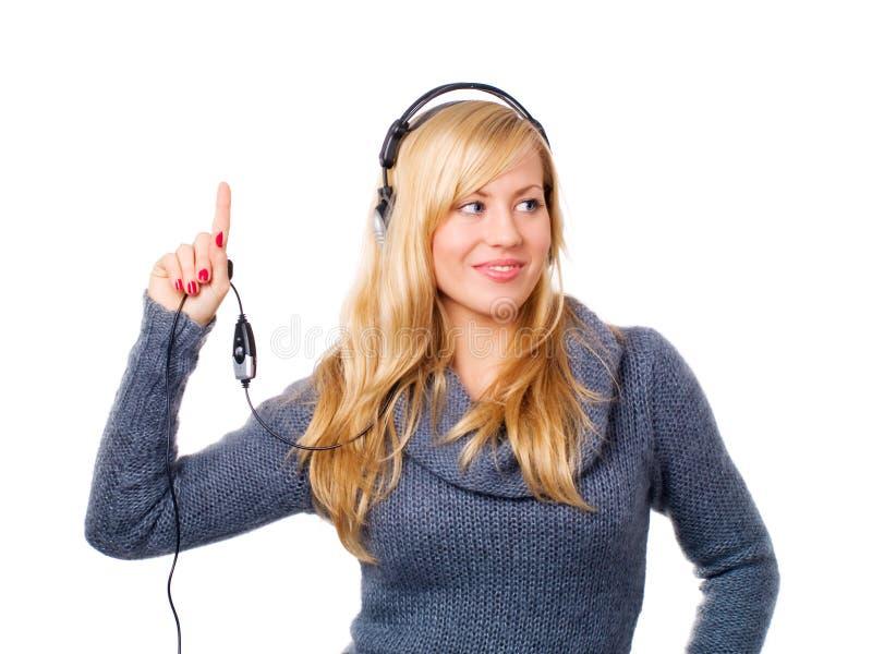指向微笑的向上妇女的耳机 免版税库存照片