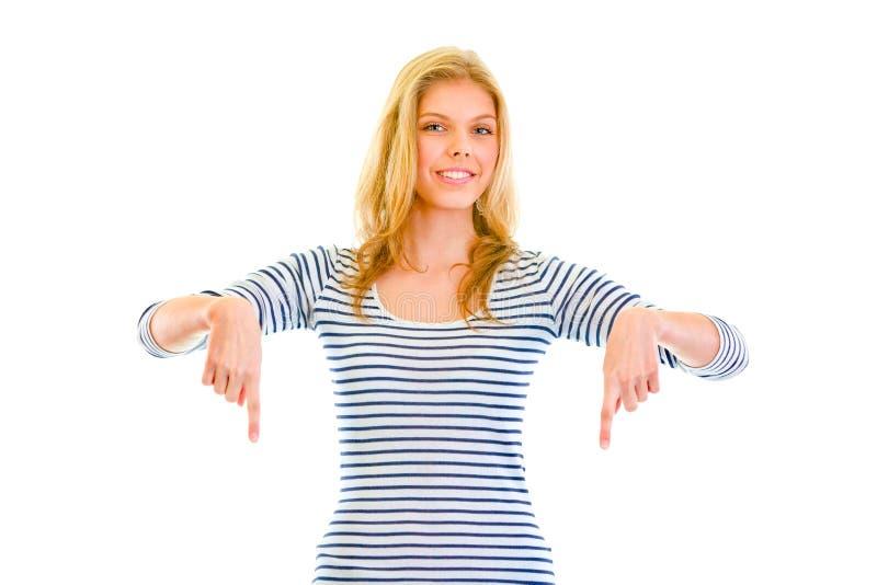 指向微笑的美丽的下来手指女孩青少&# 免版税图库摄影