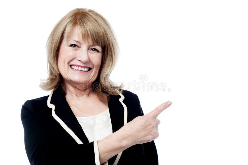 指向微笑的年迈的妇女  库存图片