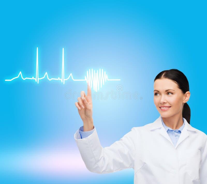 指向心电图的微笑的女性医生 免版税库存图片