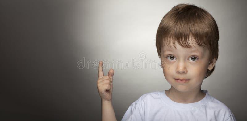 指向快乐的小男孩,愉快的孩子有好想法 免版税库存图片
