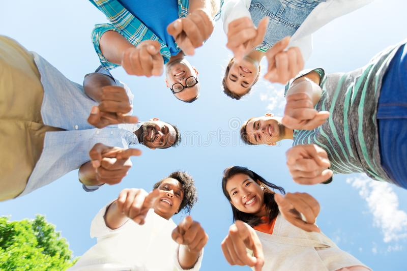 指向您的愉快的朋友站立在圈子 免版税图库摄影