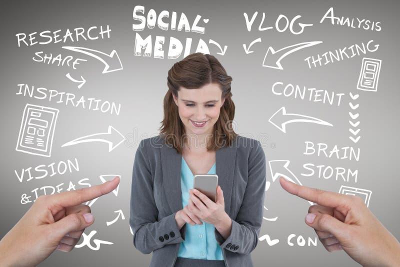 指向愉快的女商人的手使用她的电话反对与社会媒介ico的灰色背景 免版税库存图片