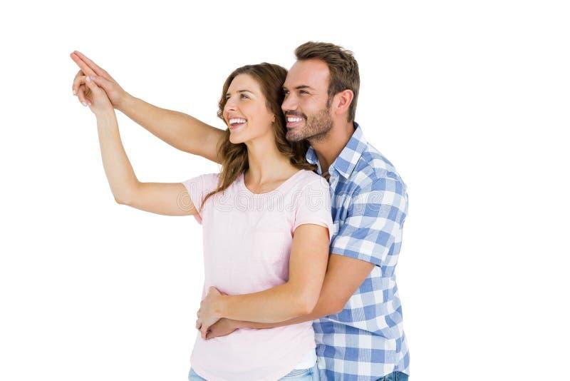 指向愉快的年轻的夫妇向上拥抱和 免版税库存照片