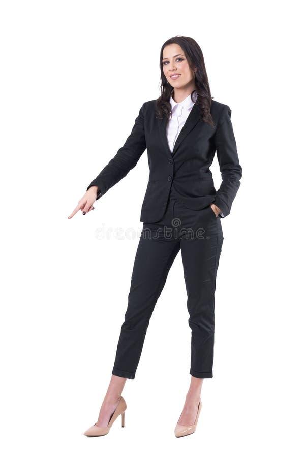 指向手指和显示在微笑的愉快的成功的女商人对照相机下 免版税库存图片