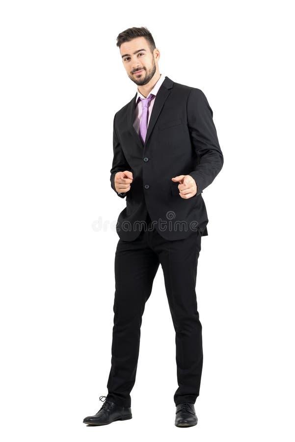 指向手指手往照相机的友好的微笑的商人枪标志 免版税库存图片
