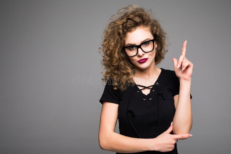 指向手指的一个微笑的女孩的画象在灰色隔绝的copyspace 库存图片