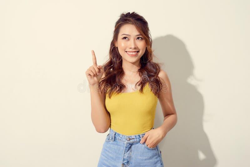 指向手指的年轻可爱的亚裔妇女 库存照片