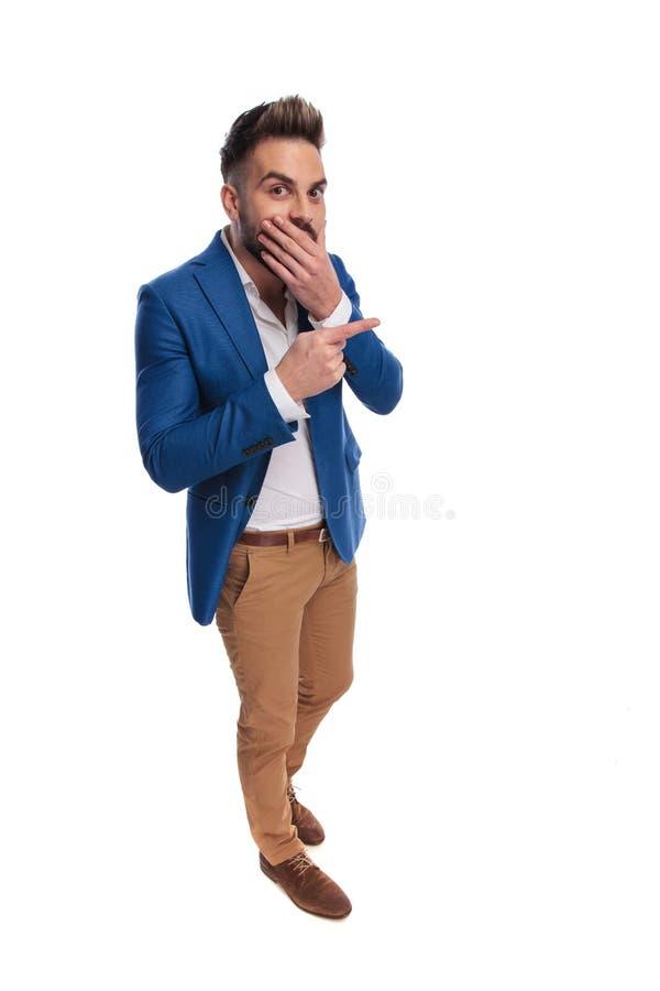指向手指的惊奇的人,当站立用手胡子时 图库摄影