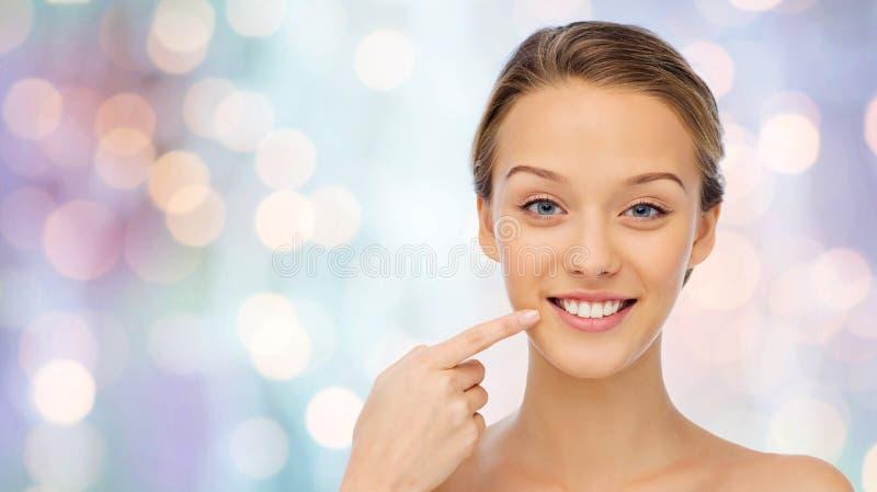 指向手指的愉快的少妇她的牙 库存照片