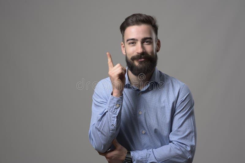 指向手指的愉快的年轻有胡子的商人向上微笑和看照相机 图库摄影