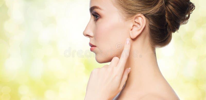 指向手指的美丽的妇女她的耳朵 免版税库存图片