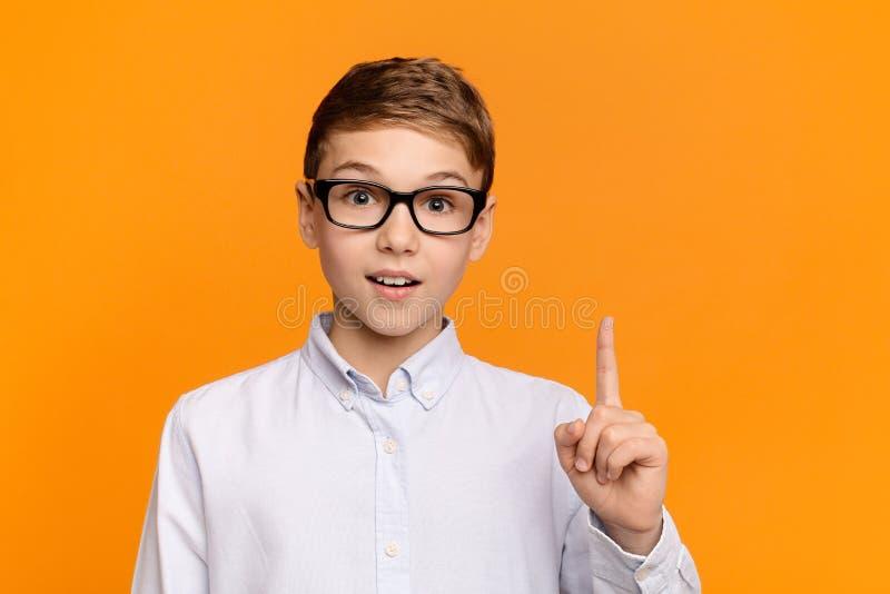 指向手指的聪明的男孩,有想法或被找到的解答 库存照片