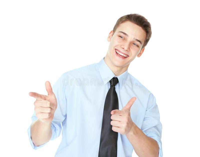 指向手指的年轻微笑的商人隔绝在白色 免版税库存图片
