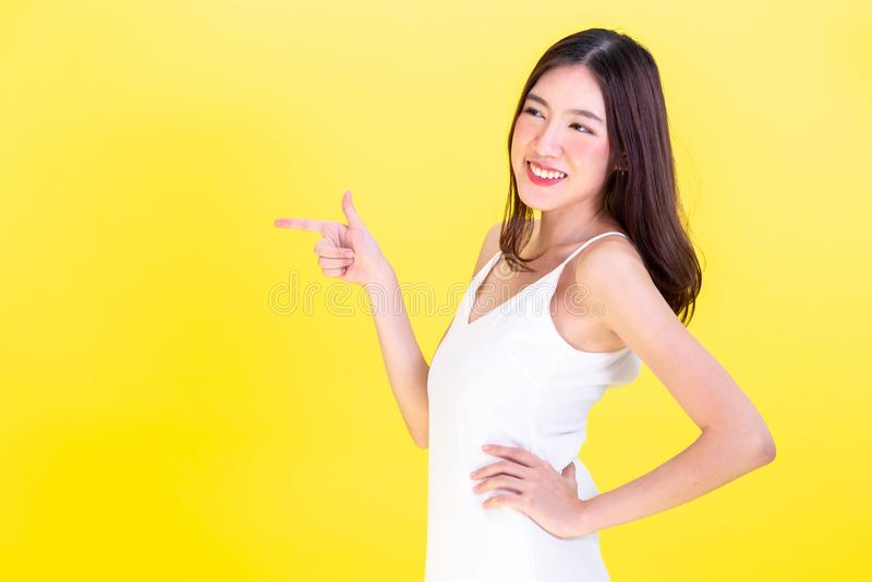 指向手空的拷贝空间和摆在胳膊的亚裔逗人喜爱的妇女两手插腰在黄色背景 库存图片
