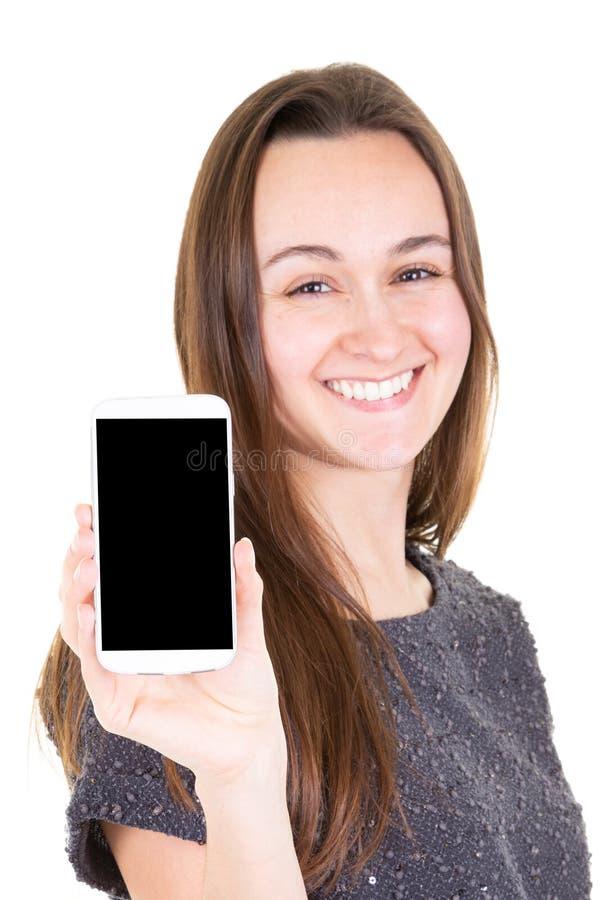 指向新的智能手机的微笑的少妇画象  图库摄影