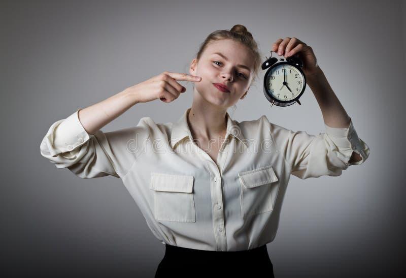 指向时钟的女孩 时钟五o 免版税库存照片