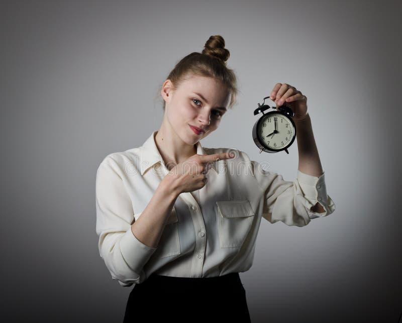 指向时钟的女孩 免版税库存图片