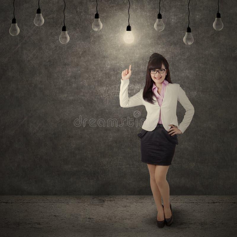 指向明亮的灯的女工 免版税库存图片