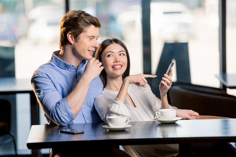 指向智能手机和看的微笑的少妇英俊的男朋友 库存图片