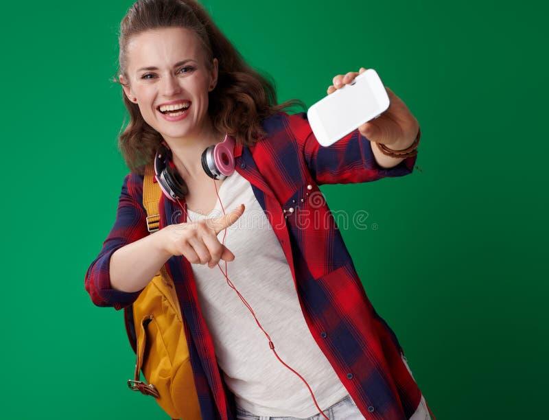 指向智能手机的学生妇女反对绿色背景 库存图片
