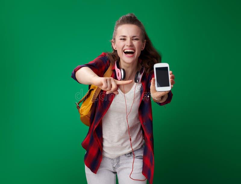 指向智能手机的愉快的现代学生妇女 免版税库存照片